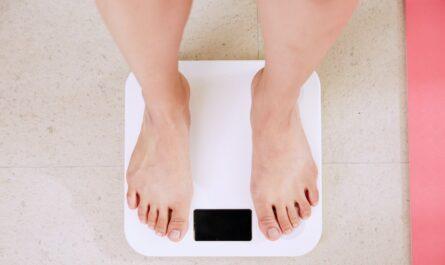 Žena stojí na váze a chce se pustit do hubnutí.